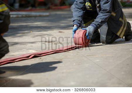 Fireman unwinding red fire hose outdoors