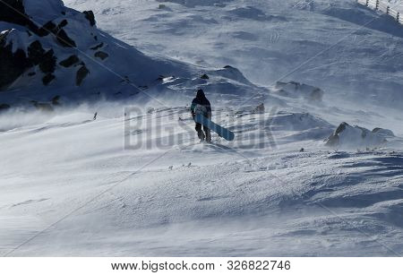 Stylish Snowboarder Walks With His Beautiful Snowboard Through Windstorm. Strong Gale Raging On The