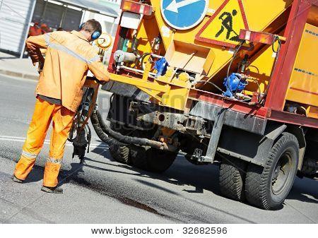 Road worker at asphalt roadway street patching reaparing work