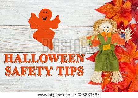 Halloween Safety Tips Message With Red And Orange Fall Leaves With A Scarecrow And Clock On Weathere