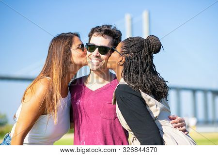 Joyful Old Friends Meeting And Having Fun Outside. Multiethnic Young Women Kissing Mans Cheeks. Mach