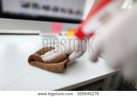 Focus On Cleaner Hand Holding Rag And Wiping Table In Modern Office. Workplace Interior With Modern