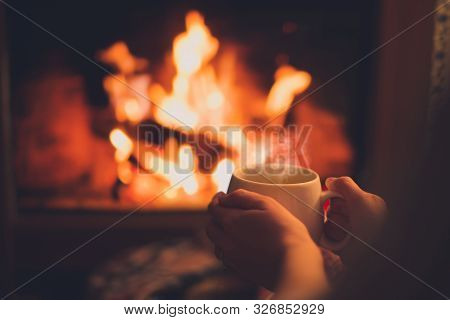 Close Up Cup Of Hot Tea In Womans Hands Sitting Near Fireplace In Cozy Room.