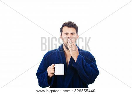 Portrait Of Tardy Young Man Wears Blue Bathrobe Holding Cup Of Coffe And Yawning Unable To Wake Up I