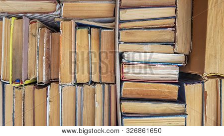 Many Sorted Old Books Are Stacked As A Background Front View. Stack Of Used Old Books In The School