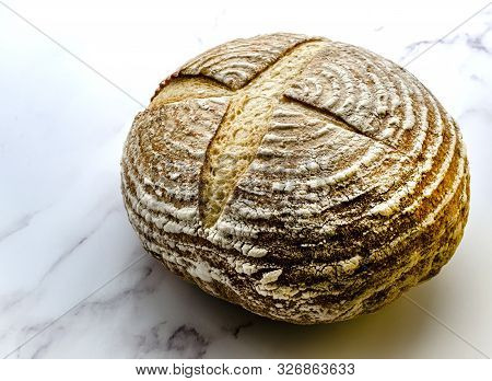 Freshly baked sourdough bread showing the traditional markings standing on a marble base poster