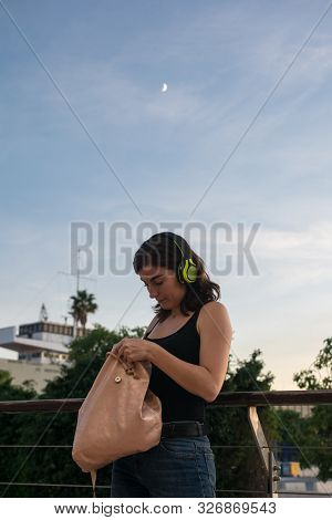 Young Woman Is Searching Something In Her Bag While She Is Listening Music