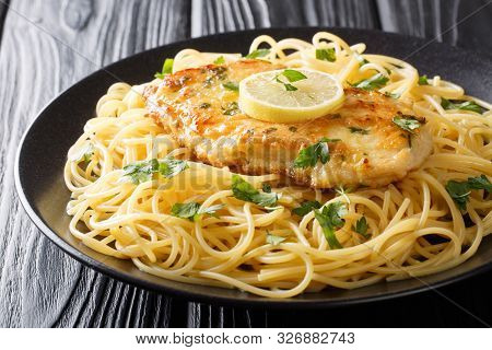 Tasty Classic Chicken Francaise With Spaghetti In Lemon Wine Sauce Close-up On A Plate. Horizontal