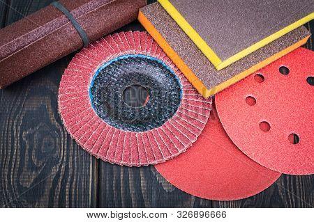 Set of abrasive tools and sandpaper different colors on black vintage wooden background poster