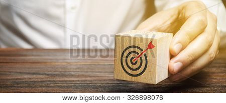 A Businessman Holds In His Hands A Wooden Block With A Target Symbol. The Concept Of Achieving Busin