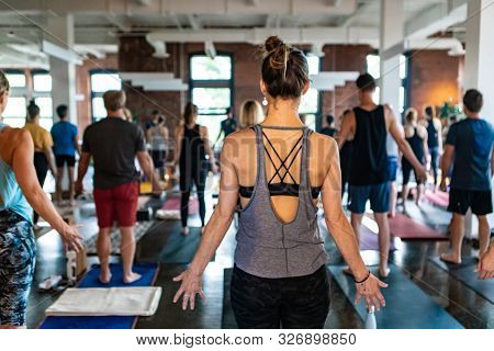 People Are Seen At An Indoor Gym Undertaking 108 Sun Salutes. A Traditional Yogic Session Practiced