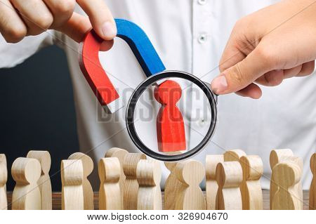 A Magnifying Glass Looks At A Red Figure Of A Man From The Crowd Pulled By A Magnet. Leader Manages