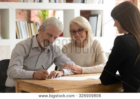 Happy Mature Clients Sign Contract Closing Deal With Banker