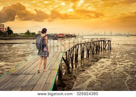 Tourist with backpack at Yeoh jetty at sunrise, Georgetown, Penang, Malaysia