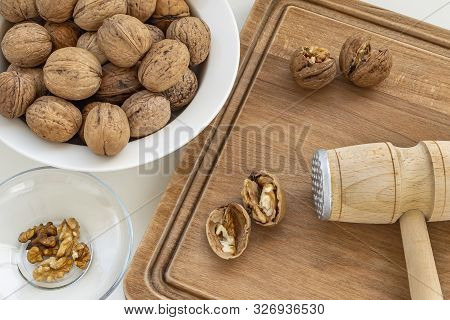 Cracked Walnuts (juglans Regia) And Wooden Meat Mallet On A Brown Wooden Board. Natural Unbleached N