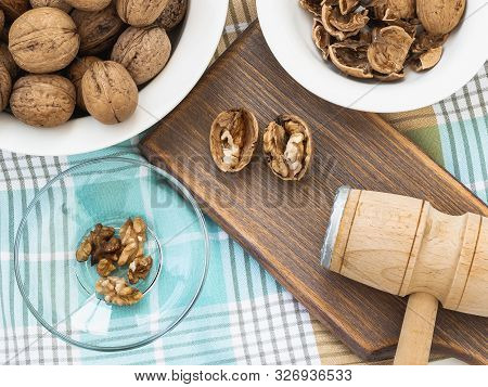 Whole Walnuts, Shells And Kernels In A Bowls Around A Brown Wooden Board With Cracked Nuts And Woode