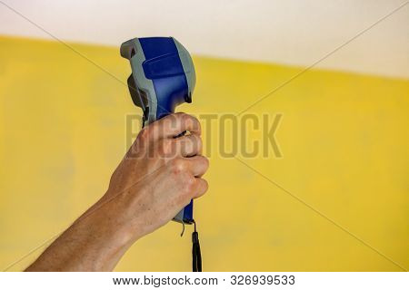 A First Person Perspective Of A Man Pointing An Infrared Thermal Imaging Device Towards A Ceiling In