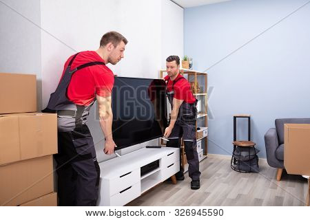 Two Male Professional Movers In Uniform Unloading Lcd Television In The Living Room