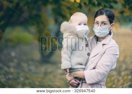 A Woman And A Small Child In Her Arms In Medical Protective Masks During The Epidemic. Mom And Baby
