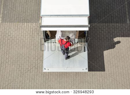 An Elevated View Of Male Mover Unloading The Furniture From Truck On Cobblestone Pavement