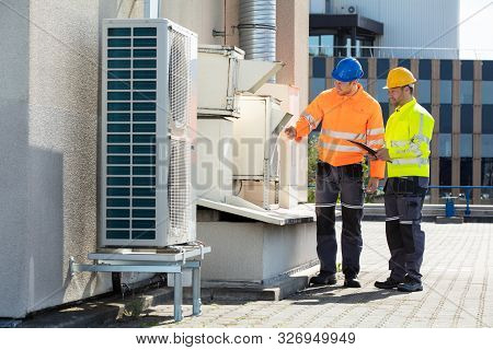 Two Electricians Men Wearing Safety Jackets Checking Air Conditioning Unit On Building Rooftop
