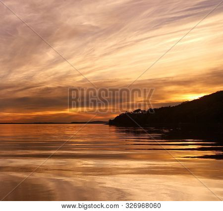 Summer Sunset With Predominately Cirrus Clouds Against A Yellow Coloured Sky Reflected In Ocean Wate