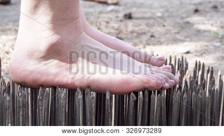 Yoga Stands On Sharp Nails In A Park Outdoors. A Close-up.
