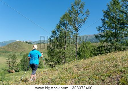 A Grown Woman On A Walk With Scandinavian Walking Sticks. The Concept Of A Healthy Lifestyle At Any
