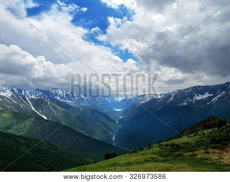 Mountainous Landscape, Lake And Mountain Range And River. Cloudy Weather And Panoramic View.