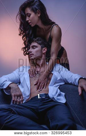 Seductive Girl In Black Lingerie Embracing Man In Unbuttoned White Shirt On Purple Background