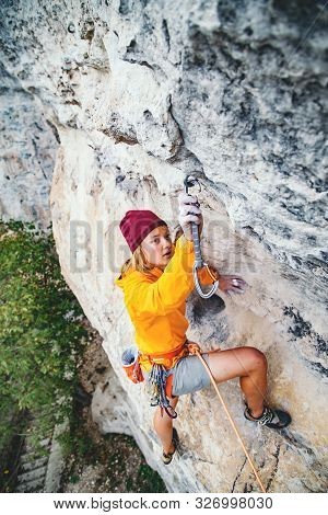 Young Woman Climbs An Overhanging Rock  With Rope And Hanging Quick Draw. Sport Climbing, Lead. Side