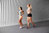fitness, sport and healthy lifestyle concept - young women or female friends with earphones wearing armbands with smartphones and running outdoors poster