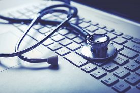 Medical Stethoscope On Laptop Keyboard. Computer Diagnostic Or E-health Concept