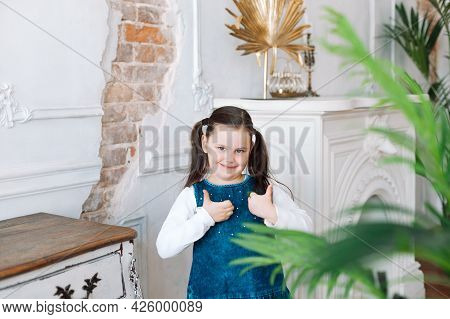 Portrait Of A Charming Girl In A Denim Dress Giving A Thumbs Up With A Fireplace And A Shabby Wall O