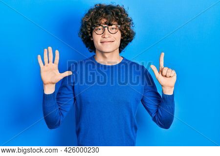Handsome young man wearing casual clothes and glasses showing and pointing up with fingers number seven while smiling confident and happy.