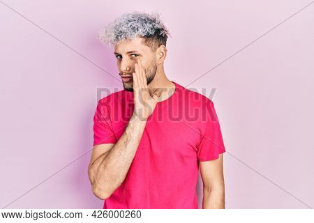 Young hispanic man with modern dyed hair wearing casual pink t shirt hand on mouth telling secret rumor, whispering malicious talk conversation