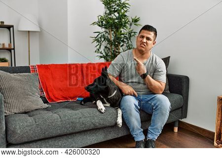Young latin man and dog sitting on the sofa at home pointing aside worried and nervous with forefinger, concerned and surprised expression