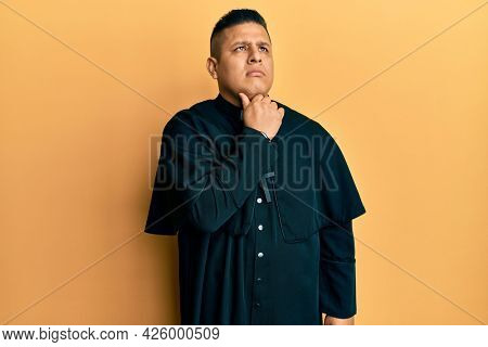 Young latin priest man standing over yellow background touching painful neck, sore throat for flu, clod and infection