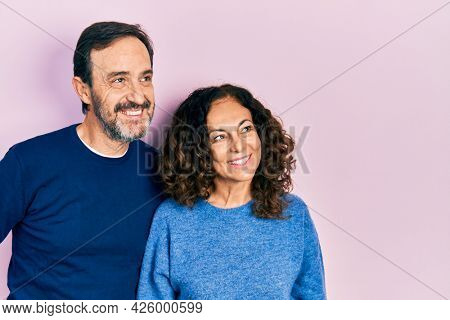 Middle age couple of hispanic woman and man hugging and standing together smiling looking to the side and staring away thinking.