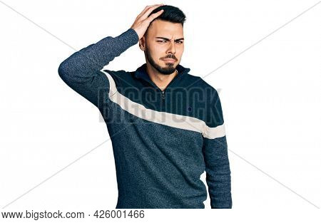 Young hispanic man with beard wearing casual winter sweater confuse and wonder about question. uncertain with doubt, thinking with hand on head. pensive concept.
