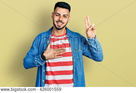 Young hispanic man with beard wearing casual denim jacket smiling swearing with hand on chest and fingers up, making a loyalty promise oath
