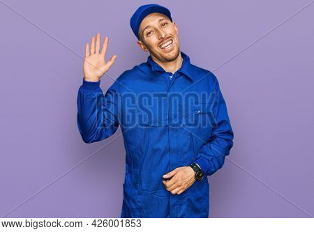 Bald man with beard wearing builder jumpsuit uniform waiving saying hello happy and smiling, friendly welcome gesture