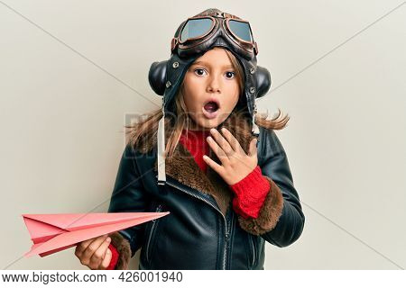 Little beautiful girl wearing pilot uniform holding paper plane scared and amazed with open mouth for surprise, disbelief face