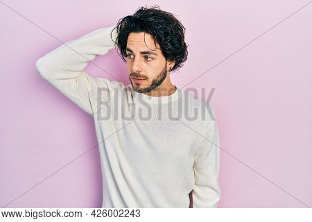 Handsome hispanic man wearing casual white sweater confuse and wondering about question. uncertain with doubt, thinking with hand on head. pensive concept.