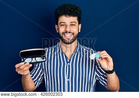 Young arab man with beard holding glasses and contact lenses smiling and laughing hard out loud because funny crazy joke.