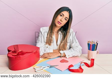Young hispanic woman making valentine gift sitting on the table looking sleepy and tired, exhausted for fatigue and hangover, lazy eyes in the morning.