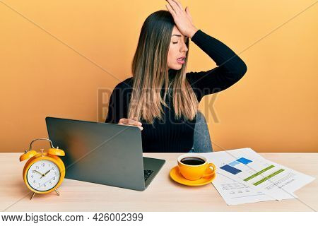 Young hispanic woman working at the office with laptop surprised with hand on head for mistake, remember error. forgot, bad memory concept.