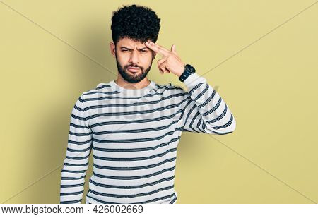Young arab man with beard wearing casual striped sweater pointing unhappy to pimple on forehead, ugly infection of blackhead. acne and skin problem