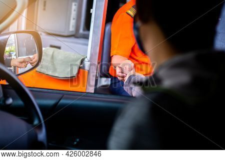 Selective Focus To Hand Of Driver Pay For The Expressway. Man Pays Money To A Cashier For A Toll Roa
