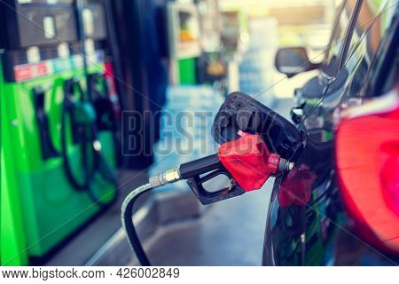 Selective Focus To Old Red Fuel Nozzle With Blurry Fuel Dispenser In Gas Station. Fill Up Fuel At Ga